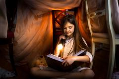 cute girl reading book in self-made house with flashlight - stock photo
