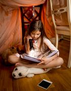 Girl sitting on floor at bedroom and reading book with flashlight Stock Photos