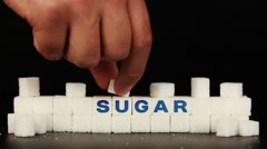 Man's hand puts sugar cubes on which is inscription the word sugar Stock Footage