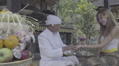 Balinese priest holding women's hand doing palm reading in temple, ungraded Stock Footage