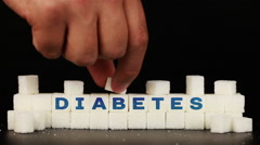 Man's hand puts sugar cubes on which is inscription the word diabetes - stock footage