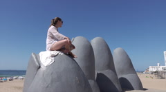 Punta Del Este, woman sits on Hand in Sand sculpture on beach, Uruguay Stock Footage