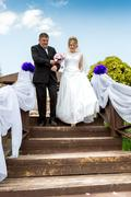 Father leading happy bride to wedding altar down the stairs - stock photo