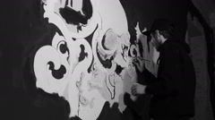 Artist painting white grafiti with skull on the black wall Stock Footage