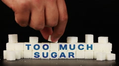 Man's hand puts sugar cubes on which is inscription the word too much sugar Stock Footage