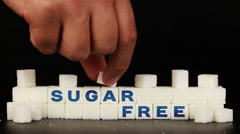 Man's hand puts sugar cubes on which is inscription the word sugar free Stock Footage