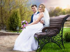 Just married couple hugging on bench at sunset Stock Photos