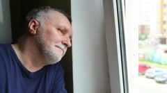 Sad serious man with grey hair thinking and looking out the window. Loneliness Stock Footage