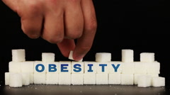 Man's hand puts sugar cubes on which is inscriptionthe word obesity Stock Footage