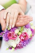Soft focus photo of groom holding brides hand on bridal bouquet Stock Photos