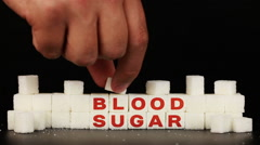 Man's hand puts sugar cubes on which is inscription the word blood sugar Stock Footage