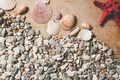 Texture of seashells and pebbles lying on wooden desk - stock photo