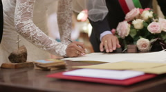 Closeup of bride and groom sign the marriage wedding contract - stock footage