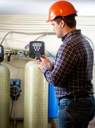 Engineer taking meter readings from industrial pumps at factory Stock Photos