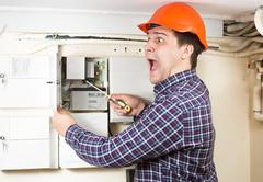 Handyman being hit by high voltage while repairing transformer Stock Photos