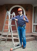 Worker posing with tools against house entrance Stock Photos