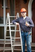 happy worker on building site holding thumbs up - stock photo