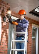 Electrician standing on ladder and changing outdoor lamp Stock Photos