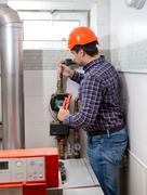 plumber in hard hat repairing heating system - stock photo