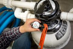 plumber checking manometer on big hydraulic pump - stock photo