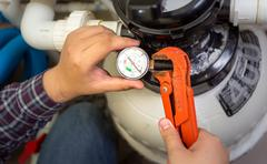 plumber installing manometer on pipe - stock photo