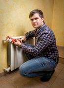 Young man holding pliers and installing radiator valve Stock Photos
