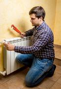 handyman fixing heating radiator with red plumber pliers - stock photo