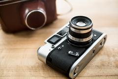 Macro photo of retro manual camera and leather case on table Stock Photos