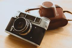 Toned photo of retro camera with brown leather case Stock Photos