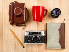 retro journalist workspace with camera, lens, notebook, pencil and cup - stock photo