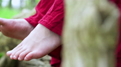 Girl with red dress on wiggling feet while sitting woods 4k - stock footage