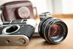 Closeup shot of retro camera, lens and leather case lying on table - stock photo