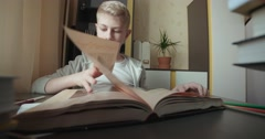 4k,Teenage boy studying - doing his homework,leafing through the book Stock Footage