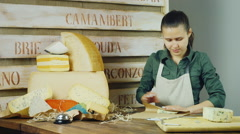 Young woman seller packs a piece of cheese at the counter - stock footage