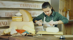 The seller cheese at work - cutting the cheese knife Stock Footage
