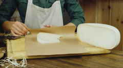 Seller hands a piece of cheese are packed in paper packaging - stock footage