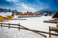 winter view of farm on mountain at Austrian town - stock photo