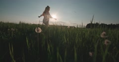 Beautiful young woman ran in the Dandelion field at sunset, slow motion Stock Footage