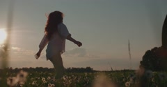 Beautiful young woman ran in the Dandelion field at sunset, the joy of life Stock Footage