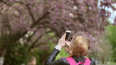 Young beautiful lady making pictures of blossoming tree in the street Stock Footage