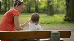 Mother and baby blowing on a dandelion on the nature in the summer in the park Stock Footage