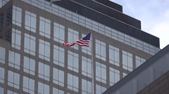 Waving US flag on the roof. Skyscraper on the background Stock Footage