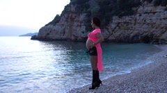 High heeled pregnant on the beach at sunset Stock Footage