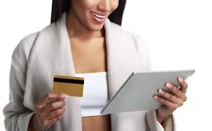 Mulatto black woman holding digital tablet computer and pay from gold credit - stock photo