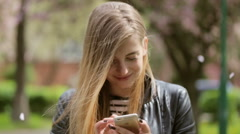 Cute young lady using her phone staying on the street Stock Footage