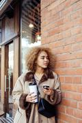 young pretty african american women drinking coffee outside in cafe, modern - stock photo