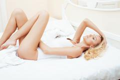 young pretty blond woman in bed covered white sheets smiling cheerful sexy look - stock photo