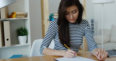 Confident brunette businesswoman taking note in a notepad at office, close-up Stock Footage