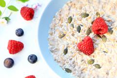 Fresh, morning cereal meal with floral arrangement and fresh fruit Stock Photos
