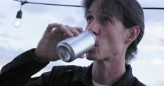 Young man drinks beer from a can in at dusk 4K Stock Footage
